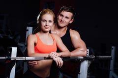 运动夫妇-男人和妇女休息在锻炼之间在健身房的杠铃附近 图库摄影
