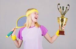 运动女孩举行网球拍和金黄觚 r 女服体育成套装备 网球员胜利 免版税图库摄影