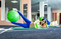 运动女孩和健康行使与在一张席子的健身球的生活方式概念在健身房 免版税库存照片