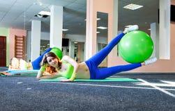 运动女孩和健康行使与在一张席子的健身球的生活方式概念在健身房 库存照片