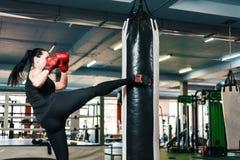 运动女孩在吊袋做反撞力 妇女在拳击手套火车武道方面 免版税库存照片