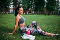 运动女孩坐一棵草在夏天公园 库存图片