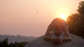 运动女孩弯曲在asana的身体在巨大的石慢动作 股票视频