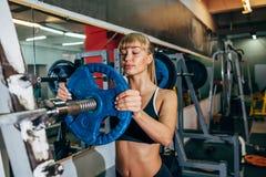 运动女孩设置在杠铃的重量在健身房 库存图片