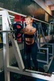 运动女孩设置在杠铃的重量在健身房 库存照片