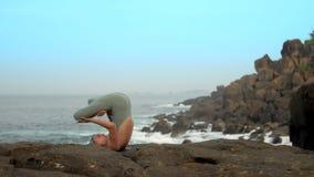 运动女孩进入在岩石慢动作的padma halasana 影视素材