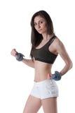 年轻运动妇女佩带的腕子重量 库存照片