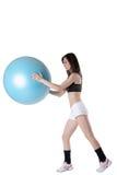 年轻运动妇女行使了与一个蓝色稳定球 库存照片