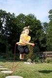 运动妇女跳绳在庭院里 图库摄影