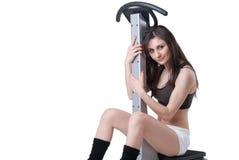 年轻运动妇女给按摩机器做广告 库存图片