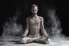 运动平静年轻人思考的盘着腿坐在瑜伽莲花姿势,与棕榈的Padmasana在mudra 库存照片
