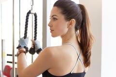运动年轻女人档案在健身房类的训练用具解决,看得在旁边,训练她的身体,有马尾,修造 库存图片