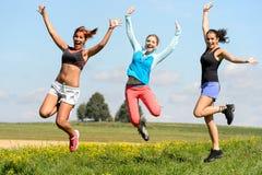 运动朋友跳跃快乐在晴朗的草甸 免版税库存图片