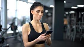 运动服卷动智能手机应用的,刺激有目的夫人 免版税库存图片