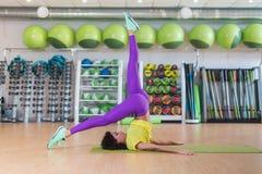 运动服实践的瑜伽的年轻运动妇女在健身房或演播室,做shoulderstand姿势,运作总之 免版税库存图片