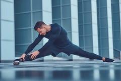 运动服的一个英俊的健身人,做舒展,当为严肃的锻炼做准备在现代城市反对时 库存图片