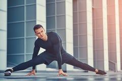 运动服的一个英俊的健身人,做舒展,当为严肃的锻炼做准备在现代城市反对时 免版税库存照片