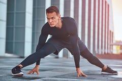 运动服的一个英俊的健身人,做舒展,当为严肃的锻炼做准备在现代城市反对时 免版税库存图片