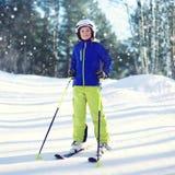 运动服的专业滑雪者儿童男孩和盔甲,晴朗的在小山山的冬天多雪的天在森林 免版税图库摄影