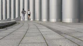 运动服的两个朋友在巨大的柱子,都市锻炼旁边一起冲刺 股票视频