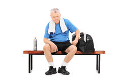 运动服的前辈坐长凳 免版税库存图片