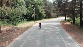 运动服的可爱的确信的年轻循环的女孩通过夏天公园乘坐 r 影视素材