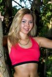 运动服的妇女在摆在公园的稀薄的桃红色T恤杉和黑紧身短裤在夏天以绿色丛生illumi 免版税库存图片
