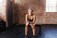 运动服的妇女坐长凳在健身房 免版税库存照片