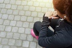 运动服的少妇检查健身跟踪仪 免版税图库摄影