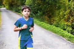 运动服的少年男孩在乡下公路跑 免版税库存图片