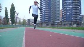 运动服的年轻人迅速跑到户外照相机在体育场健康生活方式附近炫耀人赛跑 影视素材