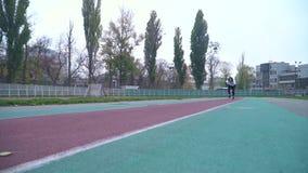 运动服的年轻人迅速跑到户外照相机在体育场健康生活方式附近炫耀人赛跑 股票录像
