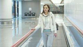 运动服的年轻女人在移动的走道努力去做在机场 影视素材