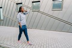 运动服的年轻确信的非洲女孩走沿街道和享受音乐的全长观点的  免版税图库摄影