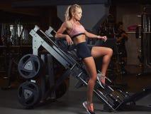 运动服的性感的嬉戏妇女在健身房的一个腿新闻机器说谎 库存照片