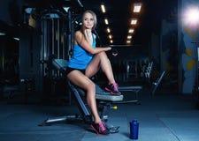 运动服的白肤金发的健身妇女有摆在健身房的完善的身体的 休息在体育锻炼以后的可爱的运动的女孩 库存图片