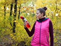 运动服的美丽的健身体育女孩有体育水瓶的或能量饮料在手中在秋天森林里 库存照片