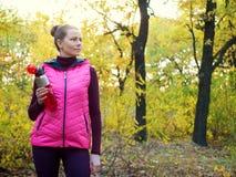 运动服的美丽的健身体育女孩有体育水瓶的或能量饮料在手中在秋天森林里 免版税图库摄影