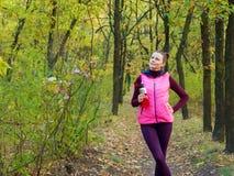 运动服的美丽的健身体育女孩有体育水瓶的或能量饮料在手中在秋天森林里 免版税库存照片