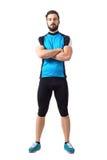 运动服的肌肉适合运动员骑自行车者有看照相机的横渡的胳膊的 免版税库存照片
