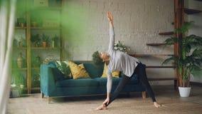 运动服的苗条少妇在家训练做瑜伽单独站立在实践集中的地板上 股票录像