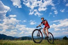 运动服的运动专业运动员循环越野的骑自行车者和盔甲骑自行车 免版税库存照片