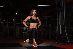 运动服的运动员女孩制定出和训练她的胳膊和肩膀与锻炼机器的在健身房 免版税库存照片