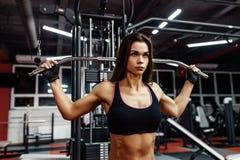 运动服的运动员女孩制定出和训练她的胳膊和肩膀与锻炼机器的在健身房 库存照片
