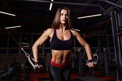 运动服的运动员女孩制定出和训练她的胳膊和肩膀与锻炼机器的在健身房 免版税图库摄影