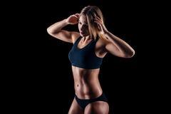 运动服的运动的女孩行使在黑背景的 被晒黑的年轻运动妇女 巨大体育女性身体 库存图片