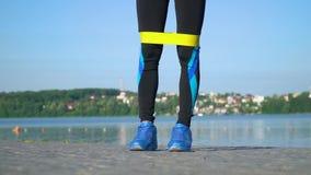 运动服的适合的运动妇女使用与舒展腿的橡皮筋和在湖附近的所有身体 少女做 影视素材
