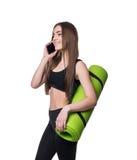 运动服的逗人喜爱的少妇有绿色席子的准备好锻炼 微笑和谈话在电话 背景查出的白色 库存照片