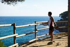 运动服的,舒展人在跑户外在山以后 人跑了距离被停下来看美丽的海 免版税库存照片