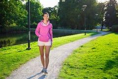 运动服的年轻亭亭玉立的妇女走在公园的 免版税库存照片